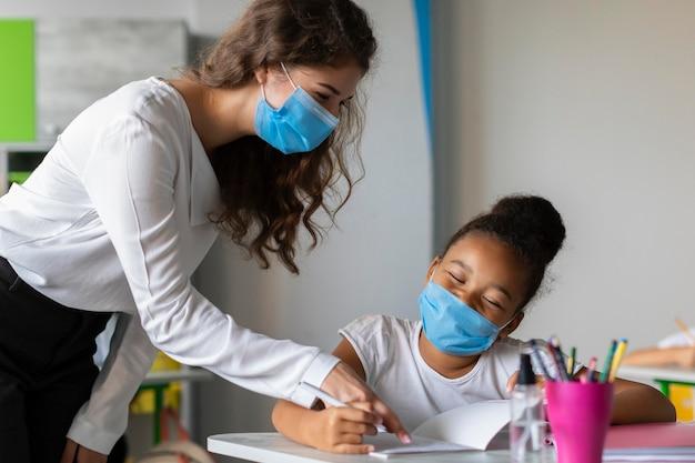 Insegnante che aiuta il suo studente mentre indossa maschere mediche Foto Premium