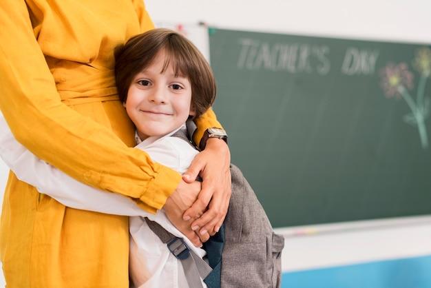 Insegnante che abbraccia uno studente con lo spazio della copia Foto Premium