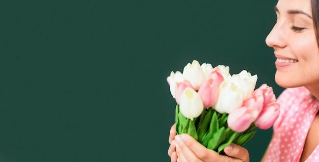Insegnante che odora un mazzo di fiori con lo spazio della copia Foto Premium