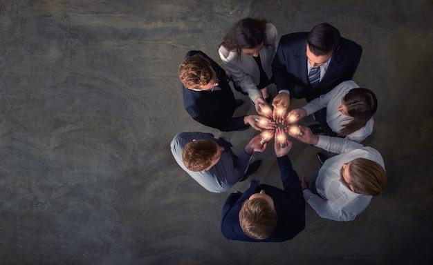 Concetto di lavoro di squadra e di brainstorming con uomini d'affari che condividono un'idea con una lampada. concetto di avvio Foto Premium