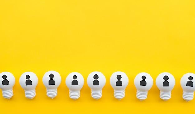 Piatto di lavoro di squadra giaceva con l'icona umana sul gruppo di lampadine in colore pastello Foto Premium