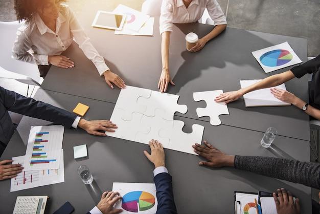 Lavoro di squadra dei partner. concetto di integrazione e avvio con pezzi del puzzle Foto Premium