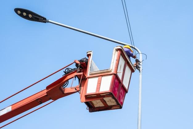 Tecnico su camion benna in alto di una gru per riparare l'illuminazione stradale. Foto Premium
