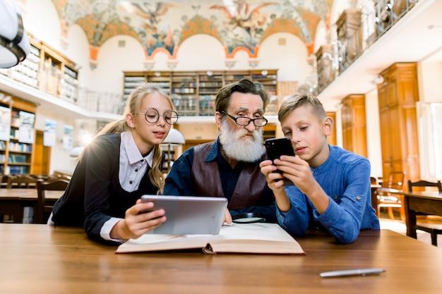 Tecnologia, computer rispetto al tradizionale concetto di libri stampati. nonno e nipoti sono seduti al tavolo in biblioteca. Foto Premium