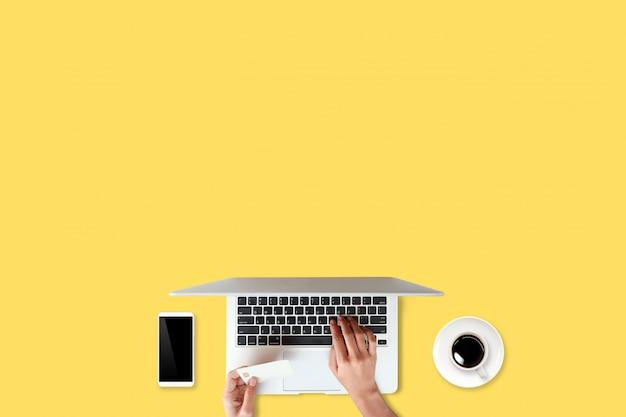 Tavolo di lavoro di tecnologia con le mani della donna sul computer portatile, carta di credito, tazza di caffè e telefono cellulare su giallo (o concetto online di acquisto e pagamento) Foto Premium