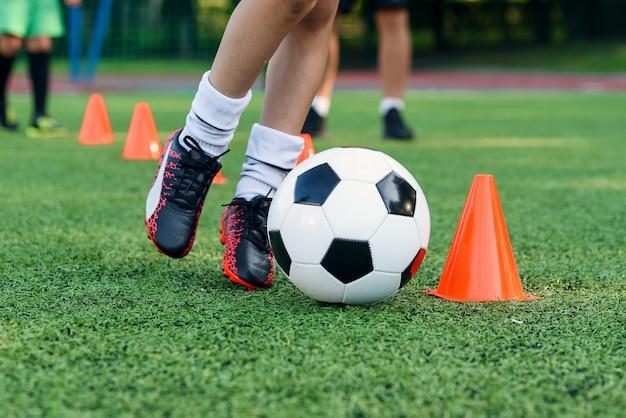 Il ragazzo teenager impara a circondare la palla tra i coni di allenamento allo stadio di calcio. Foto Premium