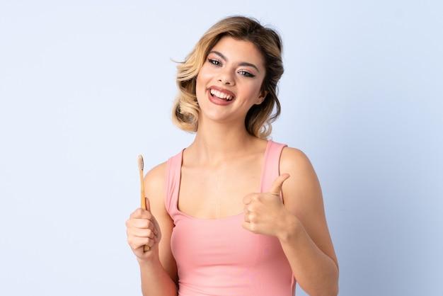 Ragazza dell'adolescente che pulisce i suoi denti isolati sulla parete blu con i pollici in su perché è accaduto qualcosa di buono Foto Premium