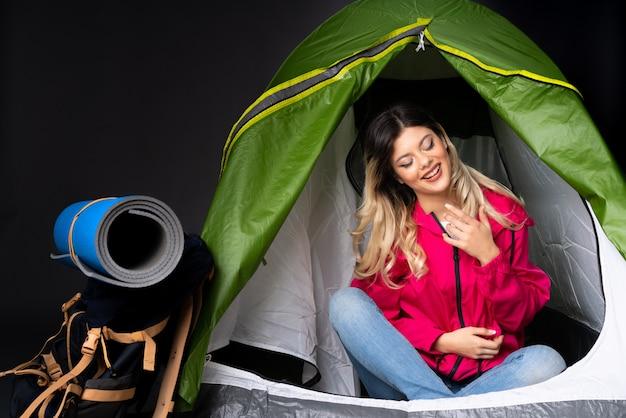 Ragazza dell'adolescente dentro una tenda verde di campeggio isolata sulla parete nera che sorride molto Foto Premium