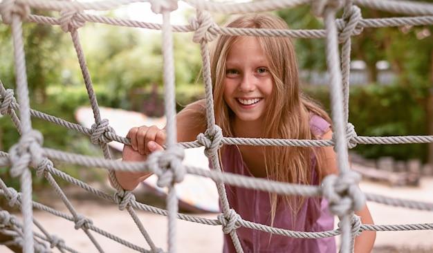 Ragazza adolescente nel parco giochi sulla scala di corda Foto Premium