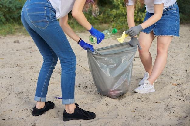 Adolescenti che puliscono i rifiuti di plastica in natura, riverbank Foto Premium