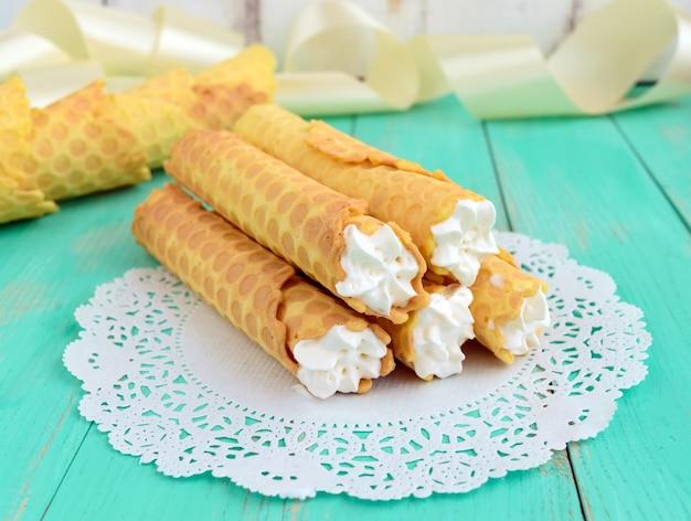 Tenero wafer al miele sotto forma di tubi, farciti con crema d'aria su tovagliolo di pizzo bianco. avvicinamento. Foto Premium