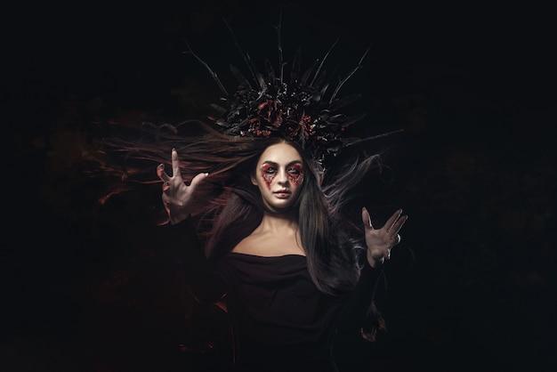 Ritratto di donna vampiro halloween orrore terribile. signora della strega del vampiro di bellezza con sangue sulla bocca che posa nella foresta profonda. fashion art design. tiene in mano una candela e legge maledizioni Foto Premium