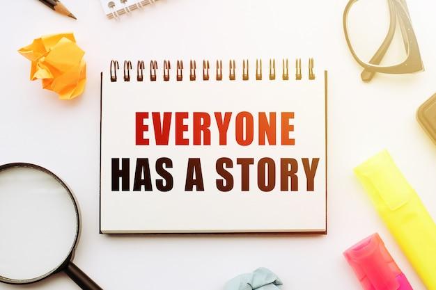Testo tutti hanno una storia in taccuino sul tavolo bianco con strumenti per ufficio Foto Premium