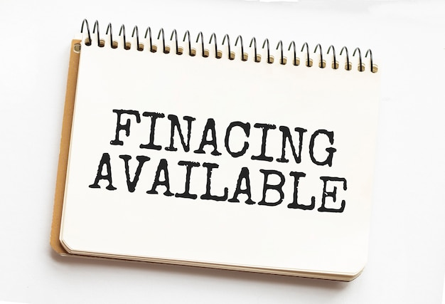 Testo finansing disponibile sulla pagina di un blocco note che si trova sui grafici finanziari sulla scrivania dell'ufficio. vicino alla calcolatrice e al pennarello. concetto di affari. Foto Premium