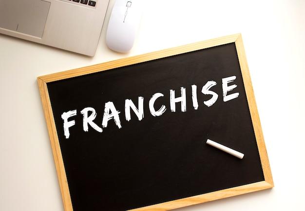 Testo franchising scritto in gesso su una tavola di ardesia. scrivania da ufficio. concetto di affari. Foto Premium