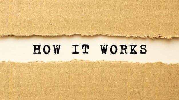 Testo come funziona che appare dietro carta marrone strappata. vista dall'alto. Foto Premium