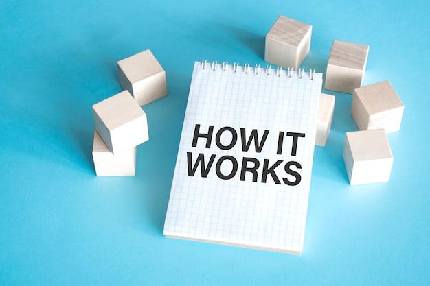 Testo come funziona sul blocco note bianco con blocco cubo Foto Premium