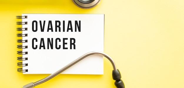 Testo cancro ovarico sul taccuino con lo stetoscopio sulla superficie gialla Foto Premium