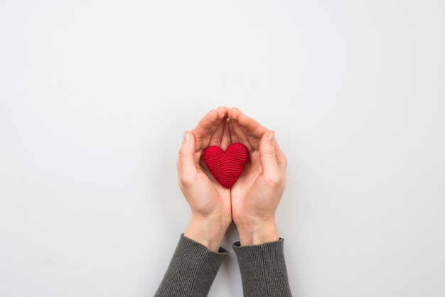 Cuore rosso del tessuto in mano della donna su fondo pastello Foto Premium
