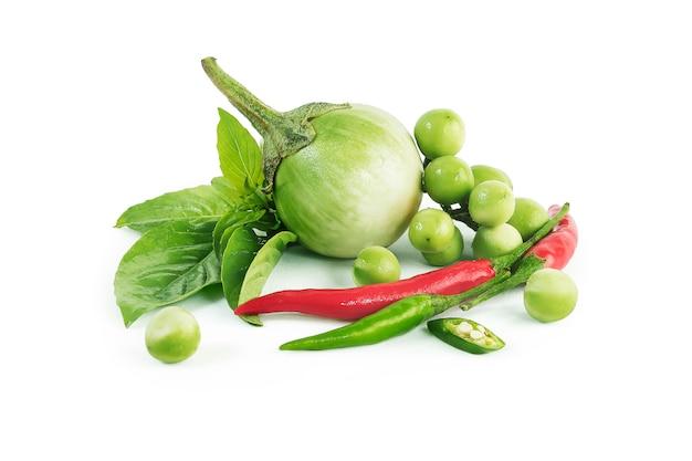 Ingredienti tailandesi del curry di verde del pollo dell'alimento isolati. melanzane in quarti, melanzane al pisello, peperoncino verde e rosso, foglie di basilico e latte di cocco. Foto Premium