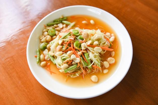 Insalata tailandese della papaya dell'alimento con le noci di macadamia sulla parte superiore sul piatto bianco Foto Premium