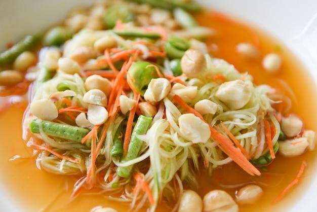 Insalata tailandese della papaya dell'alimento con le noci di macadamia sulla parte superiore sulla zolla bianca Foto Premium
