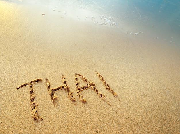 Lettere tailandesi scritte a mano in sabbia sulla spiaggia Foto Premium