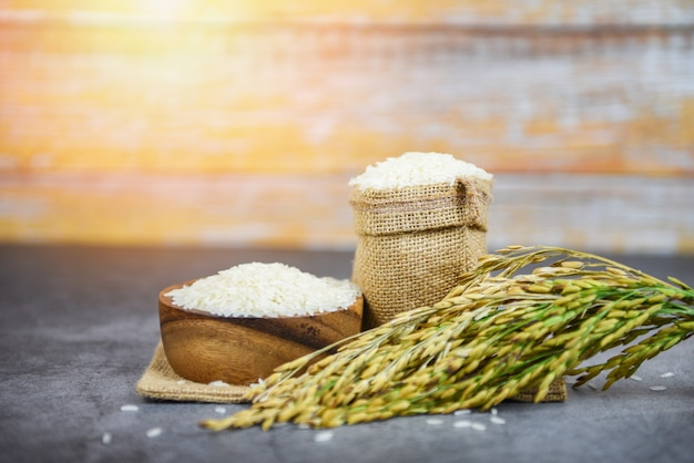 Bianco tailandese del riso sulla ciotola e sul sacco - grano crudo del riso del gelsomino con l'orecchio dei prodotti agricoli della risaia per alimento in asiatico Foto Premium