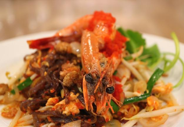 Tagliatelle di riso in padella stile tailandese saltati in padella o pad thai condita con gamberi serviti Foto Premium