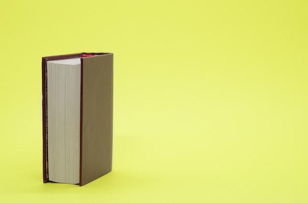 Libro spesso sulla parete gialla Foto Premium