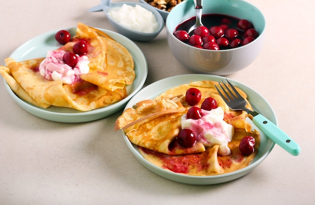Frittelle sottili con yogurt e ciliegia, servite Foto Premium