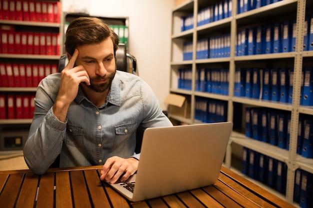 Uomo d'affari premuroso utilizzando laptop in archivio di archiviazione Foto Premium