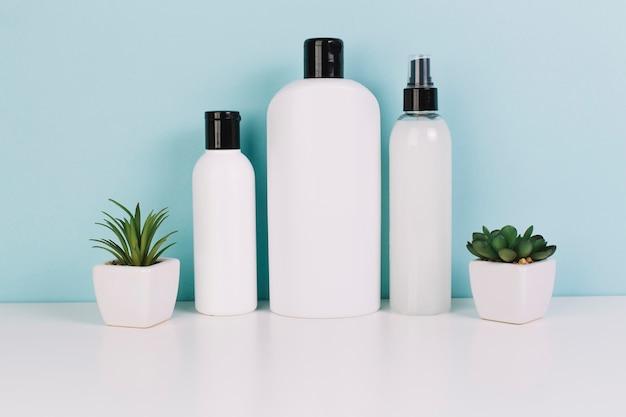 Tre bottiglie di cosmetici vicino alle piante Foto Premium