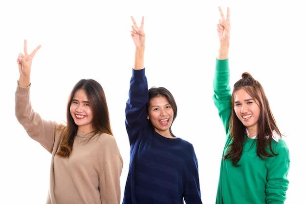 Tre amici felici della giovane donna asiatica che sorridono mentre danno il segno di pace con il braccio alzato insieme Foto Premium
