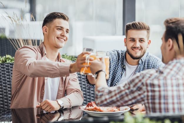 Tre persone in una bella giornata, tifano al bar sulla terrazza estiva con birre Foto Premium