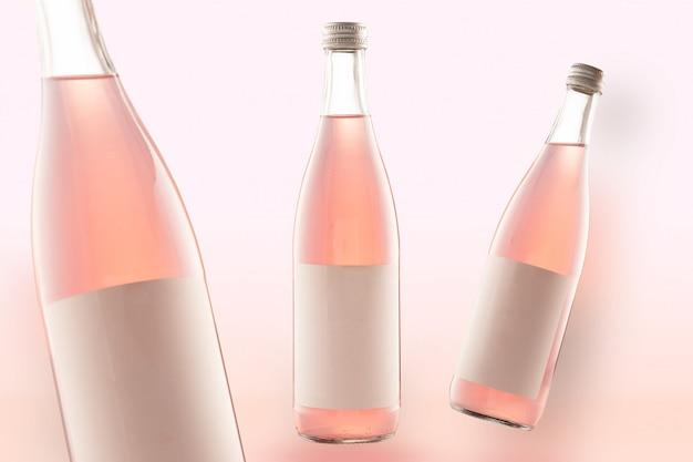 Tre bottiglie rosa di bevande mockup-cola, vino o birra. etichette bianche vuote Foto Premium