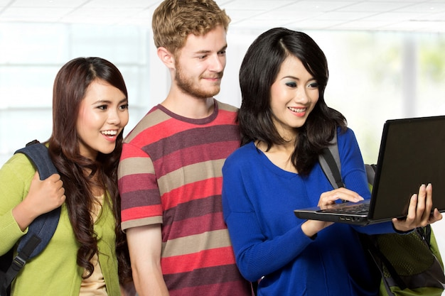 Tre studenti in cerca di un computer portatile Foto Premium