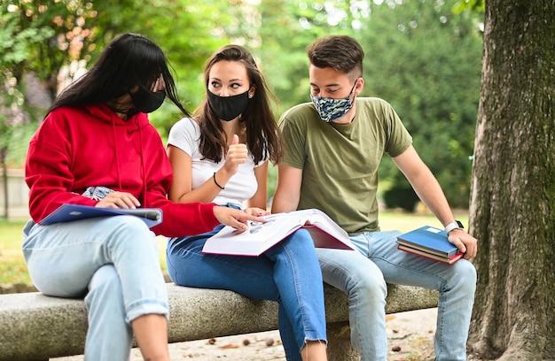 Tre studenti che studiano insieme seduti su una panchina all'aperto e indossano maschere durante il periodo del coronavirus Foto Premium