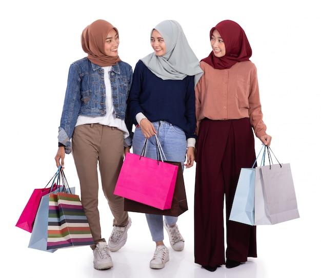 Tre donne velate eccitate quando trasportavano un sacco di carta Foto Premium