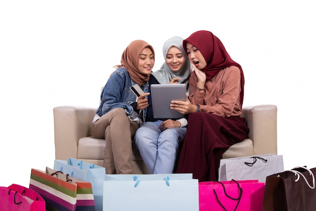Tre donne velate seduti vicino a sacchi di carta e in possesso di carta di credito per l'acquisto in un negozio online Foto Premium
