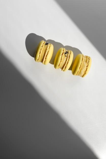 Tre amaretti francesi di limone giallo o dessert di macarons su sfondo bianco con raggi di luce dalla finestra. Foto Premium