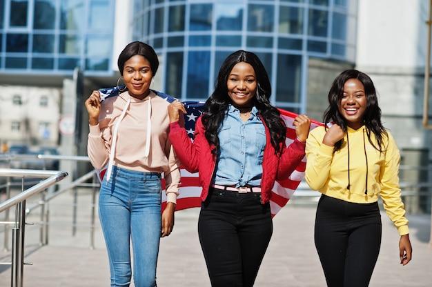Tre amici della donna afroamericana del college giovane con la bandiera degli stati uniti. Foto Premium