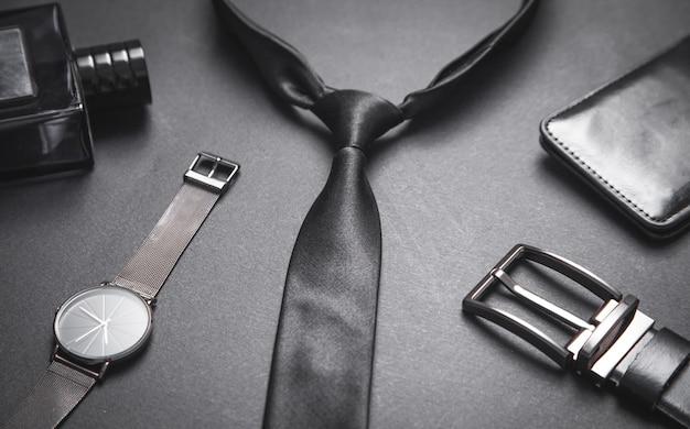 Legare con un orologio da polso e un profumo sulla superficie nera. accessori da uomo Foto Premium