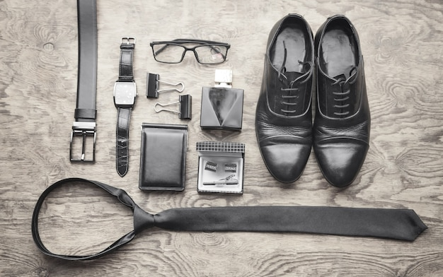 Cravatta, orologio da polso, profumo, cintura, portafoglio, scarpe sullo sfondo nero. accessori da uomo Foto Premium