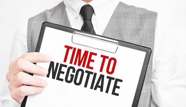È ora di negoziare l'iscrizione su un taccuino nelle mani di un uomo d'affari Foto Premium