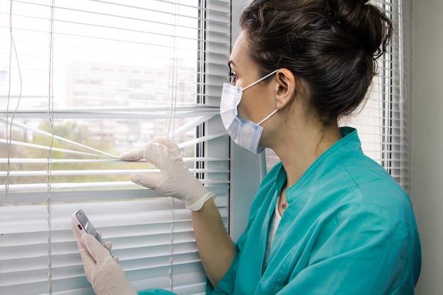 Stanco medico donna italiana in maschera medica, guanti e tuta medica guarda pensieroso fuori dalla finestra Foto Premium