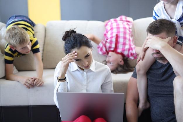 Uomo e donna stanchi sono seduti sul pavimento con il laptop che tiene la testa con la mano dietro di loro sul divano che i bambini si abbandonano. Foto Premium