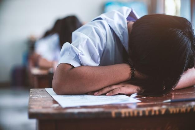 Studente stanco uniforme che dorme in un'aula di prova d'esame Foto Premium