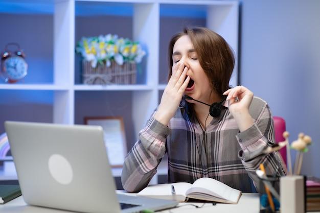 Donna stanca che sbadiglia, seduto al tavolo con il portatile, studente pigro a fare i compiti, preparando a passare l'esame, ragazza assonnata che lavora al computer dopo una notte insonne, mancanza di sonno e noia concetto Foto Premium