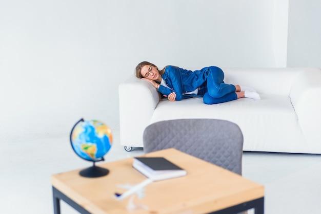 La giovane studentessa stanca in abbigliamento casual dorme sul sofà bianco. bella donna che riposa dopo una dura giornata di studio o di lavoro. Foto Premium